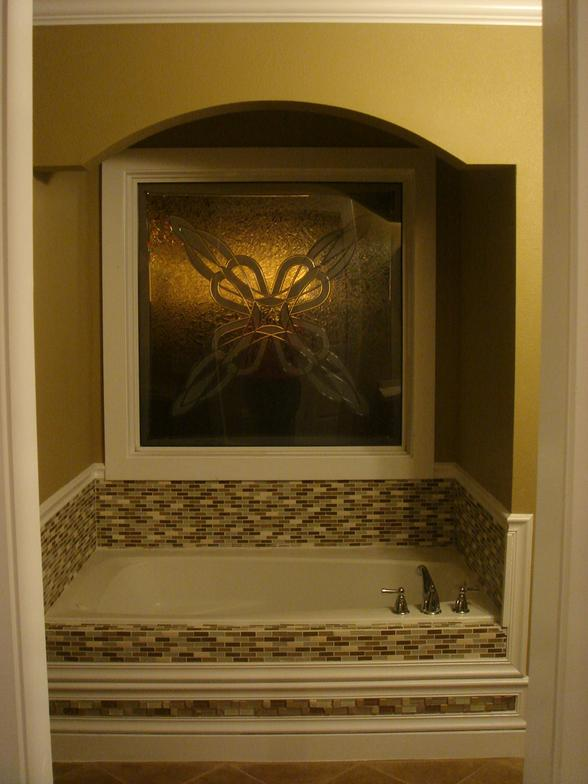 Custom tile work, an arched surround, and a great picture window make this bathroom inviting.