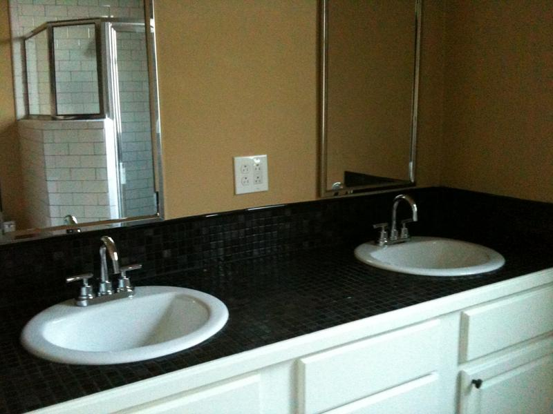 Dual sink, tiled vanity with subway tiled shower in background