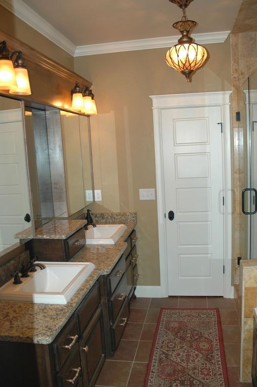 This bathroom retreat has granite counters, large square sinks, and great lighting.